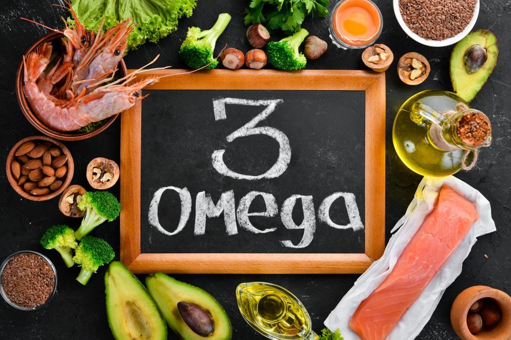 Fisch, Nüsse und Avocado auf einem Tisch mit einer Tafel auf der Omega 3 geschrieben steht